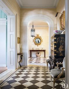 As seen from the entrance hall, a Regency mirror from Mallett is mounted in the stair hall, above an 18th-century table | archdigest.com