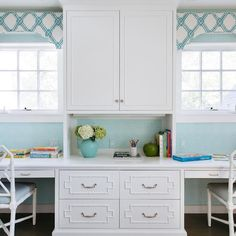 White and turquoise blue home office features white cabinets accented with bamboo overlay trim flanked by built-in desk paired with white bamboo chairs with Quadrille Java Java Wallpaper under windows dressed in white and turquoise trellis cornice boxes.