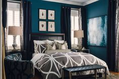 """The inspiration for the color scheme was the pool and outdoor spaces just off the bedroom. """"We chose a deep blue for the walls to create a modern feel and drew inspiration from the spirit of a gentleman's library,"""" Wheeler says. """"We utilized dark woods to create a sense of masculinity. The custom headboard with a leather insert is the focal point of the room."""