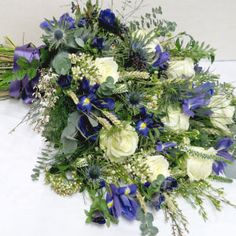 Wild, Scottish and Natural Hand-tied Sheaf includes flowers such as Iris, Waxflower, Veronica and Roses mixed with textural elements such as blue Thistles and Eucalyptus.