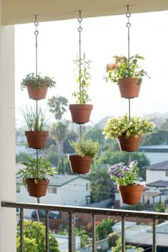 7 Gardening Tricks for Smaller Spaces Hang 'em High #smallspaces #garden #housebeautiful Tutorial link: http://thehorticult.com/turn-your-clay-pots-into-a-vertical-garden-our-dark-ryewhole-foods-collabo/