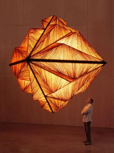 Illuminated amber color Pyramid lighting sculpture suspended in air