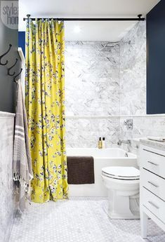 Charming contemporary bathroom features carrera marble hex tile floors leading to a drop in tub fitted with a polished nickel tub filler mounted to a carrera marble shower surround lined with marble pencil tiles.