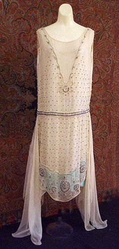 n the 1920's, the lady of means could go to an upscale store like Bonwit Teller and purchase this Paris-made dress. The beautiful beading, custom tailored to the shape of the style, the extravagant skirt panels, and the two-tone under slip are characteristics of limited edition production.