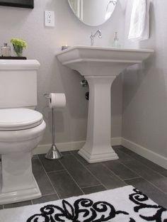 white bath dark floor pedestal sink modern bathroom