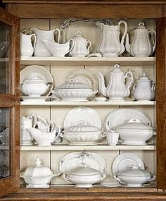 Gorgeous display of white dishes in a natural cabinet.