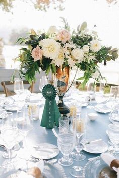 equestrian wedding tablescape with silver horse trophy and ribbon with flowers for a center piece. Great for a kentucky derby party too.