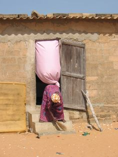 In a village in Senegal...sweeping the front steps...