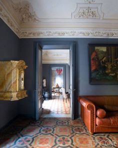 In the drawing room of Mehall Griffey and Jerry Maggi's home in Catania, Italy, the stucco ceiling and painted concrete-tile flooring are both original to the building. The sofa is by Baxter, the antique tabernacle is Austrian, and the 18th-century Flemish painting was found at a Paris flea market. The walls are painted in Farrow & Ball's Down Pipe. - ELLEDecor.com