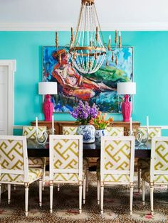 The walls (painted Poolside Blue by Benjamin Moore) take their color cue from the oil painting above the buffet. The antique chairs were updated with wipe-clean Sunbrella fabric in a graphic print. Color Trick: A pair of vintage plaster pagoda lamps painted high-gloss fuchsia (Peony by Benjamin Moore) ties the pink in the leopard-print Stark rug to the rest of the room.