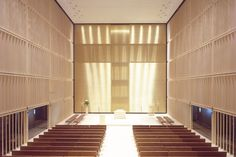 The maple slats inside are spaced to maximize the flow of daylight into the area near the altar, and the glass panels outside shift from transparent to opaque for privacy. A walkway between the two boxes also depicts the Stations of the Cross.