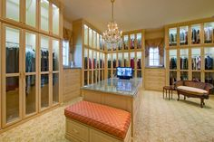 Glass doors with ample lighting, windows, huge island with a tv and many areas to lounge... true luxury when it comes to enjoying your fabulous closet  Sharif & Munir Photos