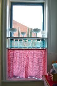 Light green walls with mason jars and a milkglass collection on window shelves above red gingham kitchen cafe curtains