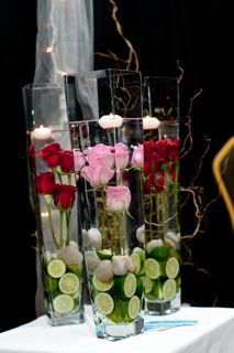 Simply stunning submerged rose centrepieces! These table centers will definitely have your guests in awe! Tall square vases filled with 4 roses, limes, river rocks and a floating candle. There are lots more ideas for wedding floral centerpieces here www.sugarbloom.ca