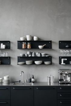 Black modular kitchen from Vipp with matching shelves on conrete walls