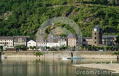 Photo made at a small town in the Rhine Valley in Germany. In the image you can be seen, over the river and a remarkable walls on the shore, a large circular structure with three openings one above the other in a dark color surrounded by housing almost all white. The hill is located at the back of the town is covered with small trees.