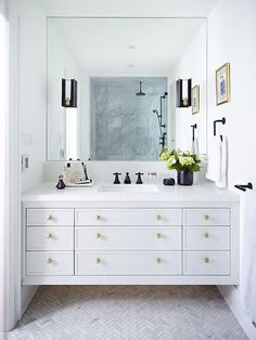 Beautifully appointed bathroom features a light gray floating washstand fixed above marble herringbone floors and fitted with brass octagon knobs and a white quartz countertop holding a sink finished with an oil rubbed bronze faucet positioned under a frameless vanity mirror lit by mirror mounted black and gold sconces.