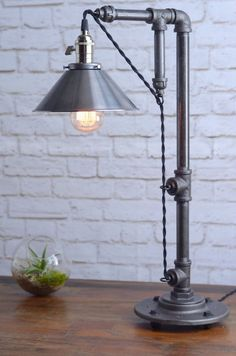 This industrial table lamp features a unique design that shows off a retro style cloth cord by running the cord through a series of pulley loops. This makes for an interesting look as well as allows the height of the shade to be adjusted. An 8 unfinished steel shade adds to the industrial style look. We use a well built vintage style socket with a turn key. The table lamp is constructed from heavy industrial black iron piping. Dimensions: Height - 26in Width - 8in Depth - 14in We packag...