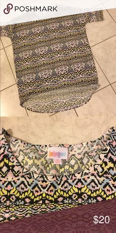 LuLaRoe small Irma Small high low tunic tee. Oversized for comfort. This has been worn twice and washed per LuLaRoe instructions, white, black, pink and yellow. LuLaRoe Tops Tunics
