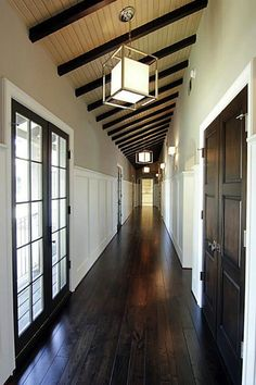 Suzie: Long, narrow corridor with glossy dark chocolate brown hardwood floors and espresso ...