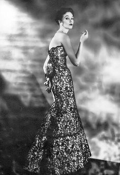 1953 Model in gown of black silk French lace over white ribbed silk, fullness swung in the back under a cascade of red roses, by Adele Simpson