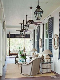 Handsome Southern porch sitting area with hanging iron lanterns and outdoor porthole wall mirrors.