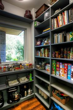 Built-in gray shelves provide ample storage for cookbooks, spices and non-perishable food items in this butler's pantry.