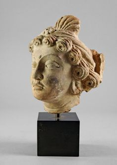 A Gandharan stucco head of a Buddha, Afghanistan c. 4th-5th century A.D. finely modelled in the round, his hair in spirals and with diadem, his face serene and with heavy lidded eyes, raised upon composite plinth, 25cm high - Price Estimate: £1000 - £1500