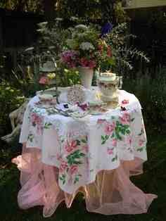 This divine floral table clothe looks great drapes over this round outdoor table. Topped with a lovely arrangement of flowers.