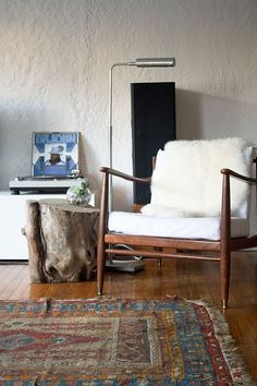 Wooden chair + white cushions + wood floor + rug + white walls + silver lamp + faux fur throw + wood side table = guest bedroom