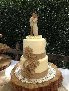Rustic Elegance. Wedding cake with burlap lace and twine flowers sitting on a wood cookie. The beautiful cake top ties it all together!