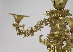 One of a set of four silver-gilt centrepieces, each with a central bowl in the form of a convolvulus flower, on a foliate stem with a wreath of flowers and four scroll branches, entwined with flowers, terminating in similar bowls. The lower section has a figure of Pan playing a pipe, a maenad playing cymbals and putti holding pan pipes and a tambourine, on a fluted circular base with lion's paw feet.