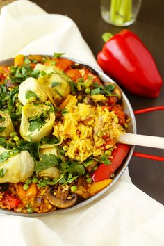 Delicious Vegan Paella, made with mushrooms, artichoke hearts, peppers and delicious saffron infused Bomba rice.