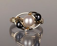 Item # WR003 Fresh water pearl with hematite bead. ( Pearl is the birthstone of June ) 21Ga. 14k Yellow gold, Gold filled or argentium silver square wires are used.