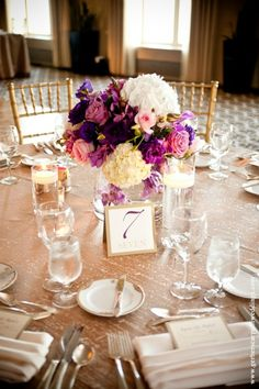 Low centerpieces of white hydrangeas, purple lisianthus, fully bloomed roses and orchids accented with floating candles