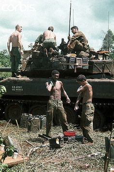 17 Oct 1969, Saigon, Vietnam --- 10/17/1969-Saigon, Vietnam- Members of the 11th Armored Cavalry in the rubber plantation area at Loc Ninh and Quan Loi Oct. 17 are shown after their arrival here. Some soldiers check out their tank as others in the foreground wash themselves off.