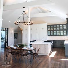 Whitewashed wood island mixed with white and dark cabinets, squirrel cage bulbs…
