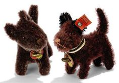 A STEIFF STANDING SCOTTY, (1308,0), black mohair, brown and black glass eyes, brown stitched nose, collar with bell and tag and FF button with red cloth tag, circa 1931 --3¾in. (9.5cm.) long (some thining and faded to reddish brown); and a similar (1310,0), collar, bell, chest tag and FF button --4¼in. (11cm.) long (faded to reddish brown)	 (2)