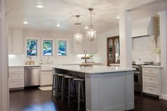The new kitchen is painted in white and soft gray, with custom cabinetry, twin chandeliers, white stone countertops, farmhouse sink, subway tile and and an antique wooden door that leads to a new butler's pantry.