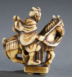 """A Japanese ivory netsuke of Oguri Hangan and the Go table. Kiyozumi, possibly from Kyoto, 19th century. Depicting Oguri Hangan (1398-1464) standing his horse with all four feet on the surface of a Go table. Himotoshi using the horse back legs. Signed: """"Kiyozumi"""" on the side of the Go table. 2 1/8""""h x 2""""w.  Note: A similar piece is illustrated in George Lazamick's """"Netsuke & Inro artists and how to read their signatures"""", page 626. Provenance: Ex. Collection of a Private US Collector."""
