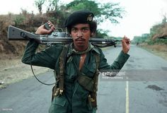 Portrait of an unidentified Salvadoran guerrilla, a Heckler & Koch G3 assault rifle across his shoulders, as he stands in the middle of a road, central El Salvador, April 1, 1983. At the time, the country was engaged in what became a 13-year Civil War between successive right-wing governments (backed by the US and others) and various armed guerrilla factions that eventually claimed over 75,000 lives before ending in 1992.