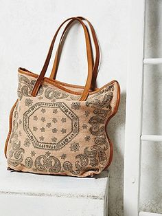 Sun Valley Tote   Printed canvas tote bag with a faded, use-to-perfection look and feel. Vegan, faux leather handles and trimming. Comes with matching mini zip purse that clasps to the inside of the bag. Spacious and chic.