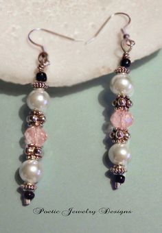 Pink Crystal and antique pearls with tiny black glass beads dangle silver colored fish hook earrings that measure 2 3/4 inches
