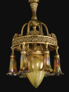 Tiffany Studios SEVEN-LIGHT CHANDELIER the central shade engraved L.C.T., each lily shade engraved L.C.T. Favrile favrile glass and gilt metallic patinated bronze 23 in. (58.4 cm) drop 13 1/4 in. (33.7 cm) diameter circa 1910