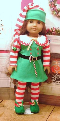 Sweet little elf costume for your American girl doll, or similar 18 inch dolls. The dress is made from cotton knit, with buttons on the front, rick rack trim, black velveteen belt and buckle, and gold ribbon bow. The dress closes in the back with velcro. Also included are her red and