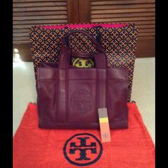 """TORY BURCH LARGE """"TORY TOTE"""" This is truly an amazing bag. The color is true violet. It is such a great color it can be carried with anything!  The bag features a side pocket on each side plus another pocket on the outside back of the bag. The inside features a zippered compartment plus two additional pockets for cell phone etc. extremely roomy. The handles are trimmed in the same color fabric. It can be used over the shoulder or hand carried. It includes dust bag and large Tory shopping…"""