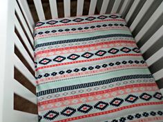 This Aztec style crib sheet features colors of navy blue, teal, coral, peach, and gray and will go perfect in your babys tribal themed