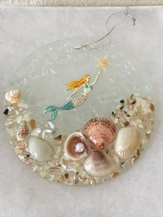 sparkling suncatcher made with seashells, sea glass, starfish, crushed shells and a beautiful mermaid reaching for the stars. Seashell Projects, Seashell Crafts, Beach Crafts, Cd Crafts, Resin Crafts, Crafts For Teens, Seashell Mobile, Sea Flowers, Mermaid Ornament