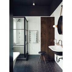 A decoração preto e branco foi o ponto alto deste projeto. Localizado em Montreal, Canadá, este banheiro de estética industrial tem ladrilho geométrico no piso e acentos de madeira, que trazem a sensação de calor ao ambiente. Projeto simples e muito agradável, não é? #design #decor #interiores