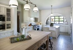 Long kitchen design features arched alcove filled with stacked, floating shelves over white cabinets topped with white marble framing farmhouse sink situated under steel windows.